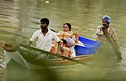 A woman and children are rescued by boat in the Kotturpuram area of Chennai.(R Senthil Kumar/ Press Trust of India vi...