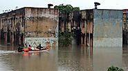 Rescue workers carry food in a boat to distribute to people trapped in a flooded residential area.(AP Photo)